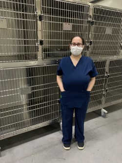 employU client standing in front of animal crates at animal shelter